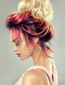 Young attractive woman is demonstrating multi colored hair gathered in elegant evening or wedding hairstyle. Hairdressing art, coloration of hair and beauty products. Portrait in profile.